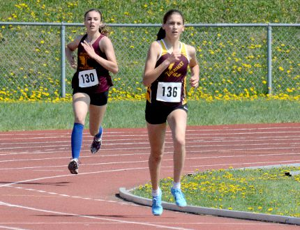 Maxine Dupuis, of École secondaire catholique Thériault, leads teammate Jordyn Bartolomucci around the bend during the 1,500 metres at the 2018 NEOAA Track & Field Championships at Timmins Regional Athletics and Soccer Complex on Wednesday. Due to the low number of entries, Midget, Junior and Senior Girls were all combined in the same event. Dupuis went on to win the Senior Girls title, while Bartolomucci captured the Midget Girls crown. THOMAS PERRY/THE DAILY PRESS