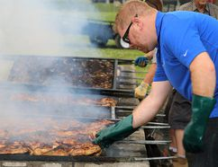 TIM MEEKS/THE INTELLIGENCER Ron Urquhart, a volunteer from Shorelines Casino, checks the temperature of chicken during the 38th annual Kiwanis Chicken BBQ Wednesday at Quinte Curling Club.