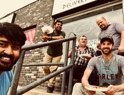FACEBOOK PHOTO Co-owner George Abraham, Tittu Chandra Bose, who helped set up the restaurant, co-owner Jim Melahrinakis, co-onwer Rob Mackay (standing) and Steven Wallace take a picutre outside the newly opened Lil Ava's Pizza.