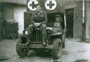 Ernie Wood sits on the hood of his WWII modified Jeep ambulance.