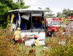 Firefighters and police officers respond to a serious collision involving a bus west of Prescott on Highway 401 on Monday. Postmedia Network