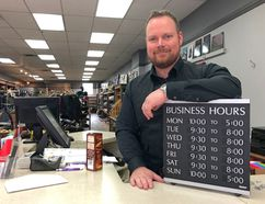 Rob Russell, owner of MacLeods Scottish Shop and head of the BIA, holds a board showing his business' new business hours; starting June 12, his store will begin closing at 8 p.m. over the next several months. JONATHAN JUHA/THE BEACON HERALD/POSTMEDIA NETWORK