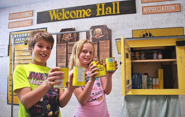 Emerson and Chloe, Grade 4 students at Gregory Drive Public School, hold up canned goods Monday next to the free little pantry they built with their class. The pantry will be stationed at the community gardens at Grand Avenue East and Victoria Avenue in Chatham starting June 23. Tom Morrison/Chatham This Week