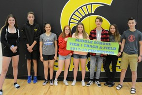 Sophie Ferguson (from left to right), Grady Hauk, Abygale Reeve, Hailey McAvena, Amanda Paquette, Owen Fitchett, Hunter Aman, and Cody Jaman stand side by side presenting a banner labelling them as champions. The track and field athletes did exceptional in this year's South-Central zone competition.