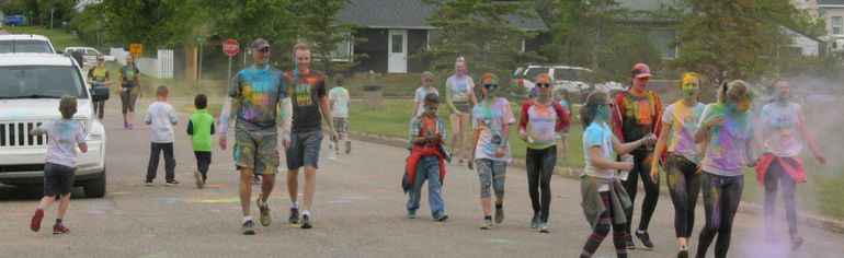 Participants in the colour run cross the finish line covered in coloured powder and smiling