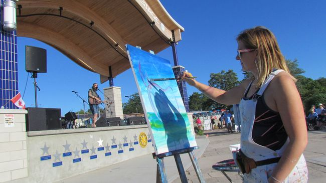 Kristyn Watterworth, with Kryart Studio in Bayfield, paints as Pat Maloney sings on the Grand Bend beach Rotary Community Stage in June 2017 during the opening night of that year's Summer Sunset Sounds concert series in Grand Bend. This year's concert series begins July 2 at the beach with South Huron Rocks. (File photo/The Observer)