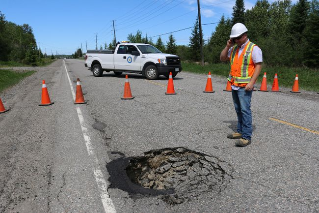 Public Works supervisor Mario Vandal inspected the sinkhole on Laforest Road caused by a culvert collapse.  LEN GILLIS / Postmedia Network