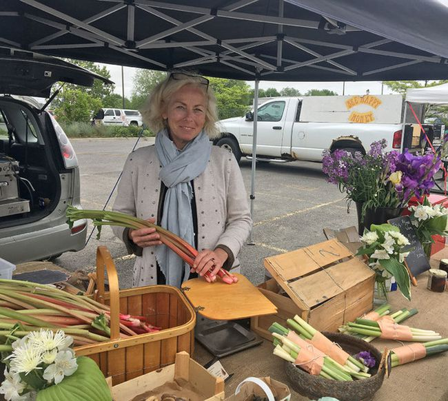 Ruthie Cummings, founder of the West Market, holds some rhubarb at her vendor tent, which offers a collection of sourdough breads in all varieties and sizes and local wild foods on Saturday June 2 2018. Sebastian Bron/The Whig-Standard