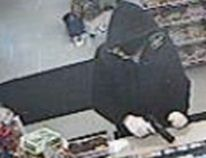 A photo released by Lambton OPP shows an alleged robbery taking place Sunday at a store in Corunna. Police are still looking for a suspect. (Handout/The Observer)