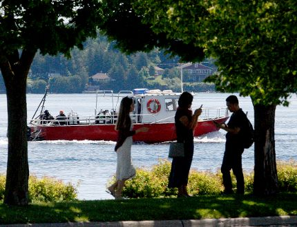 A dive boat goes west along Brockville's waterfront while Yiyi Zheng, left, a Chinese student in Ottawa, and her parents from China, Huihong Zhu and Baiqin Zheng, take pictures on Blockhouse Island on Friday. (RONALD ZAJAC/The Recorder and Times)