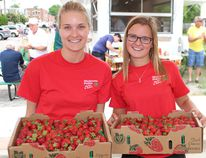 Ally Glaves (left) and Sierra DeMaere from Wholesome Pickin's strawberry farm showed off the June berry batch at the Delhi Strawberry Festival on Saturday. Susan Gamble/The Expositor