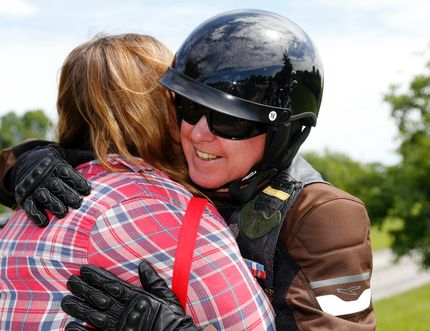 Motorcyclist Robert O'Hara of Sydenham, Ont. hugs Angela Roddy of Hillier before the third-annual Darren Williams and Wayne Boone Memorial Ride Saturday in Hillier. A car struck riders of the 1 Canadian Army Veterans motorcycle group in 2015, killing Williams and Boone and injuring O'Hara badly. Roddy and her husband, Chris, ran from their nearby home to help.