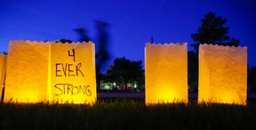 Participants in the 2018 Relay for Life in Belleville walk past luminary candles dedicated to people fighting cancer or who have died from it.