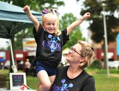 Amie Bell, right, holds up her daughter Kerrigan outside the Eight Count Cheer Academy tent at Tecumseh Park during CK Summer Fest Saturday. (Tom Morrison/Postmedia Network)