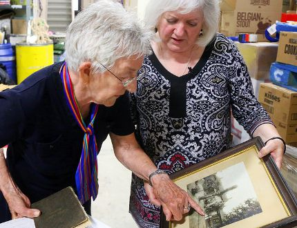 Luke Hendry/The Intelligencer Lois Foster of Belleville points out a relative in a 1909 photo of her husband's family as Susanne Quinlan listens Monday at Gleaners Food Bank in Belleville. The photo was found among items donated for the food bank's July yard sale. Foster learned of its discovery after Quinlan contacted The Intelligencer in an attempt to find descendants of those in the picture.