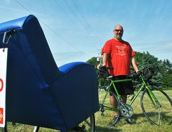 Ralph Zuke, president of the Fairview Heights Rotary Club, is shown Saturday at Adel Farms in Jeannettes Creek with the Barcalounger rickshaw bicycle he is riding from St. Louis, MO to Toronto for the Rotary International Convention. Tom Morrison/Chatham This Week