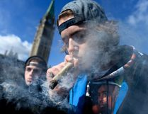 A man smokes a marijuana joint during the annual 4/20 celebration on Parliament Hill in Ottawa on Friday, April 20, 2018. The Canadian Press/Justin Tang
