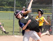 Sean Chase/Daily Observer Our Lady of Lourdes catcher Olivia Mahon (left) leaps to grab the ball as an Eganville runner attempts to reach homeplate. The RCEIAA West Grade 7 three-pitch championships was held on June 12 at the Petawawa Civic Centre.