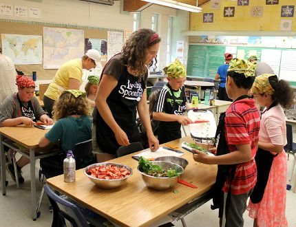 Anne Munier, Loving Spoonful's GROW Project co-ordinator, helps students chop strawberries and spinach. Centennial Public School students and volunteers harvested their garden on Monday. Students and volunteers prepared a salad bar with their homegrown produce. (Sebastian Bron/The Whig-Standard)
