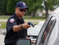 Firefighter John McNutt pitches in Saturday during hospice car wash fundraiser at North Bay Toyota.