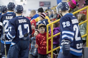 Kids line up to high five the Eagles hockey players, including a boy with lights on his sweater, during the Canmore Eagles AJHL game against the Calgary Mustangs on Family Day at the Canmore Recreation Centre on February 19, 2018. Pam Doyle/www.pamdoylephoto.com.