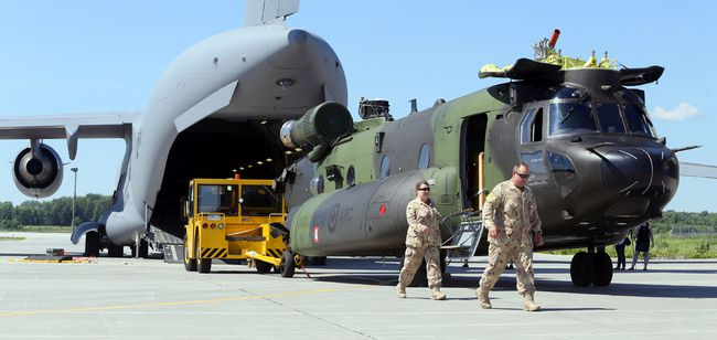 """Sgt. Shannon Cormier and Warrant Officer  David Brewer, both of 450 """"Viking"""" Tactical Helicopter Squadron, walk past a CH-147F Chinook helicopter Tuesday, July 3, 2018 at Canadian Forces Base Trenton, Ont. Technicians from the Petawawa, Ont.-based squadron and Trenton's 2 Air Movements Squadron were loading the Chinook aboard a CC-177 Globemaster III transport. It's the first of three Chinooks heading for the Canadian mission in Mali. Luke Hendry/Belleville Intelligencer/Postmedia Network"""