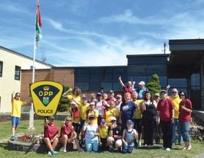Photo by KEVIN McSHEFFREY/THE STANDARD The group of Special Olympics athletes, police officers and supporters pose for a photo in front of the OPP detachment office in Elliot Lake.