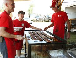 On the right, Huron East firefighter Steve Eckert mans the sausage grill on Canada Day at the Huron East Fire Station in Seaforth for the popular Seaforth Fire Fighter's Breakfast. (Shaun Gregory/Huron Expositor)