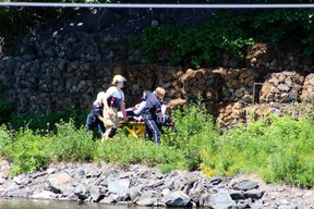 Northwest EMS transport a patient to a waiting ambulance while emergency responders continue to search for possible drowning victims in the vicinity of the railway bridge at McLeod Park, Thursday, July 5. Reg Clayton/Daily Miner and News