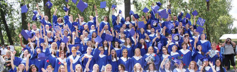 IAN GUSTAFSON HIGH RIVER TIMES/POSTMEDIA NETWORK. The 2018 graduating class of École Secondaire Highwood High School throw their hats in the air.