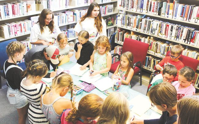 Instructor Naomi Jersch, left, and Lexi McConnell, right, help the kids do arts and crafts at the Nanton Thelma Fanning Memorial Library during the TD Summer Reading Club Wednesday, July 4th. This event will take place every Wednesday afternoon until Aug. 15.