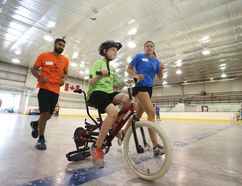 Cropboxes Web Featured Two volunteers help a participant during iCan Bike Camp, a week-long program that teaches kids with disabilities how to ride a two-wheeled bike. Meghan Balogh/The Whig-Standard