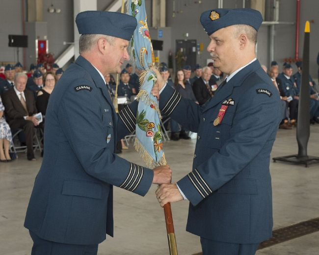 Cpl. Zebulon Salmaniw/8 Wing Imaging Lieutenant-Colonel Philip Marcus, incoming Commanding Officer, 424 (Transport and Rescue) Squadron receives the Squadron's colour from Colonel Mark Goulden, 8 Wing Commander during a change of command parade held at 8 Wing Trenton.