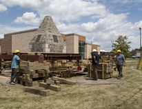 A crew from Continental Building Movers works to gradually lower a 48-ton stone monument to its new location at the County of Brant fire administration building on Dundas Street East in Paris. (Brian Thompson/The Expositor)