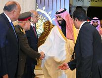 A handout picture released by the Egyptian Presidency on March 4, 2018, shows Saudi Arabia's Crown Prince Mohammed bin Salman, centre, shaking hands with Egyptian officials upon his arrival in Cairo. MOHAMED SAMAAHA/Getty Images