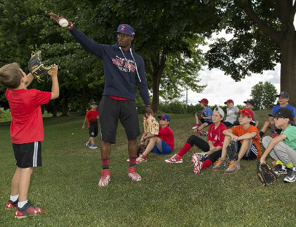 DeAndre Asbury-Heath, of the Brantford Red Sox, works on the proper technique to catch a fly ball with six-year-old Luke Duran on Wednesday during a Red Sox baseball camp. (Brian Thompson/The Expositor)