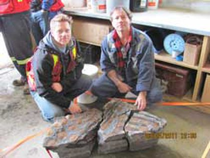 Shawn Funk, right, the shovel operator who discovered the fossil, and his supervisor Michel Gratton (left) pose with a piece of the prehistoric bones found at Suncor. (Photo supplied)