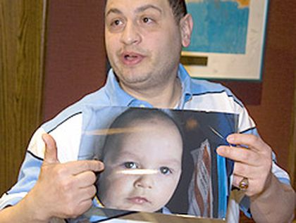 Moe Maraachli holds a photo of his son, Joseph. Atracheotomy was performed on the baby at a hospital in St. Louis, Mo., Monday. (QMI Agency file photo)