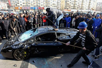 Onlookers take pictures and videos as workers use sledgehammers to smash a Lamborghini Gallardo car. The luxury vehicle was ordered destroyed by the disgruntled owner after he got into a dispute with the auto company about maintenance issues. REUTERS