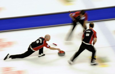 Ontario skip Glenn Howard (left) curls against Manitoba with his lead Craig Savill and second Brent Laing (right) during the final game at the Brier curling championships in London, Ontario, March 13, 2011. (MARK BLINCH/REUTERS)