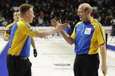 Alberta skip Kevin Martin celebrates with second Marc Kennedy (left) after they defeated Northwest Territories/Yukon during the 13th draw at the Brier curling championships in London, Ontario, March 10, 2011. (Mark Blinch/REUTERS)
