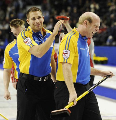 Alberta skip Kevin Martin celebrates with third John Morris after they defeated Northwest Territories/Yukon during the 13th draw at the Brier curling championships in London, Ontario, March 10, 2011. (Mark Blinch/REUTERS)