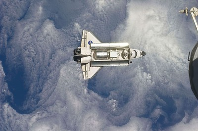 The space shuttle Discovery is seen with Earth in the background as the shuttle approaches the International Space Station for docking in this February 26, 2011 photograph by an Expedition 26 crew member released by NASA. REUTERS/NASA