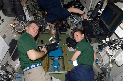 NASA astronaut Catherine Coleman and European Space Agency astronaut Paolo Nespoli of Italy get ready to take photos through the windows of the Zvezda Service Module of the International Space Station during rendezvous and docking activities of space shuttle Discovery in this February 26, 2011 photo released by NASA. REUTERS/NASA