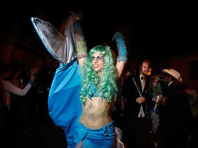 Vanessa Tolino is dressed as a toxic mermaid and chained to a man dressed as an oil executive in a reference to last year's BP oil disaster in the Gulf of Mexico, during the Krewe du Vieux Mardi Gras parade in New Orleans, Louisiana, Feb. 19, 2011. REUTERS/Lee Celano
