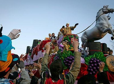 New Orleans Saints' quarterback Drew Brees, dressed as King of Bacchus, prepares to throw a toy football during the Bacchus Mardi Gras parade in New Orleans, Louisiana, Feb. 14, 2010. REUTERS/Lee Celano