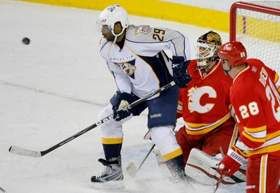 Joel Ward of the Nashville Predators eyes a shot in front of Calgary Flames goalie Miikka Kiprusoff and Robyn Regehr during NHL action at the Scotiabank Saddledome in Calgary on Sunday March 6, 2011. LYLE ASPINALL/CALGARY SUN/QMI AGENCY
