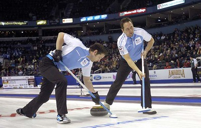 Quebec second Christian Bouchard, left, and third Robert Desjardins sweep during a second draw game against Nova Scotia on opening day at the 2011 Tim Horton's Brier at the John Labatt CentreMORRIS LAMONT / THE LONDON FREE PRESS / QMI AGENCY