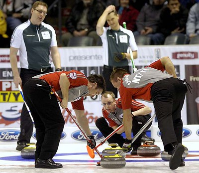 Northwest Territories/Yukon lead Marty Gavin, left, and second Brad Chorostkowski sweep while third Tom Naugler lines up the shot with PEI skip Eddie MacKenzie, left, watching during a second draw game  on opening day at the 2011 Tim Horton's Brier at the John Labatt Centre MORRIS LAMONT / THE LONDON FREE PRESS / QMI AGENCY