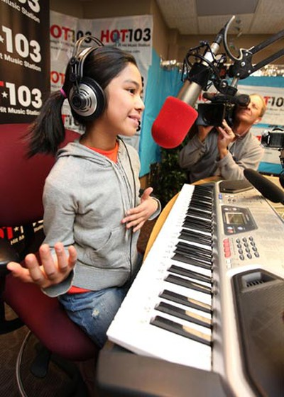 Young singer Maria Aragon (left), 10, answers a question in the HOT 103 studio in Winnipeg from host Ace Burpee (not shown) Feb. 17, 2011. (MARCEL CRETAIN/Winnipeg Sun)